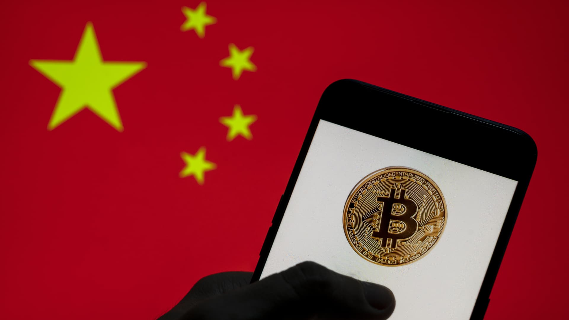 In this photo illustration, the Bitcoin logo is seen on a mobile device with People's Republic of China flag in the background. (Photo Illustration by t/SOPA Images/LightRocket via Getty Images)
