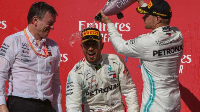 Rekan setimnya pembalap Mercedes AMG Petronas Motorsport Valtteri Bottas (77) dari Finlandia menuangkan sampanye ke kepala pembalap Mercedes AMG Petronas Motorsport Lewis Hamilton (44) dari Inggris Raya setelah merebut gelar lanjutan Kejuaraan Dunia Formula 1 FIA 2019