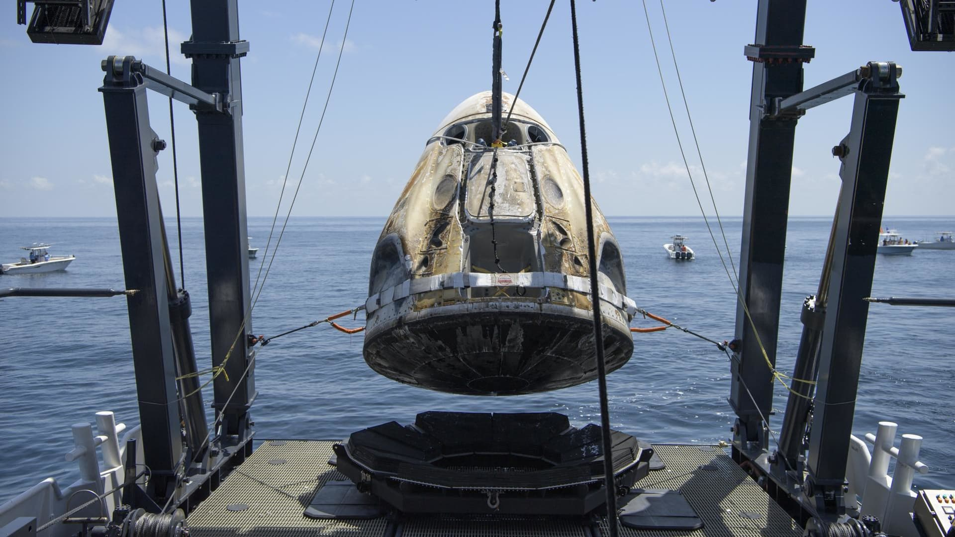 The SpaceX Crew Dragon Endeavour spacecraft is lifted onto the SpaceX GO Navigator recovery ship shortly after it landed with NASA astronauts Robert Behnken and Douglas Hurley onboard in the Gulf of Mexico off the coast of Pensacola, Florida, Sunday, Aug. 2, 2020.