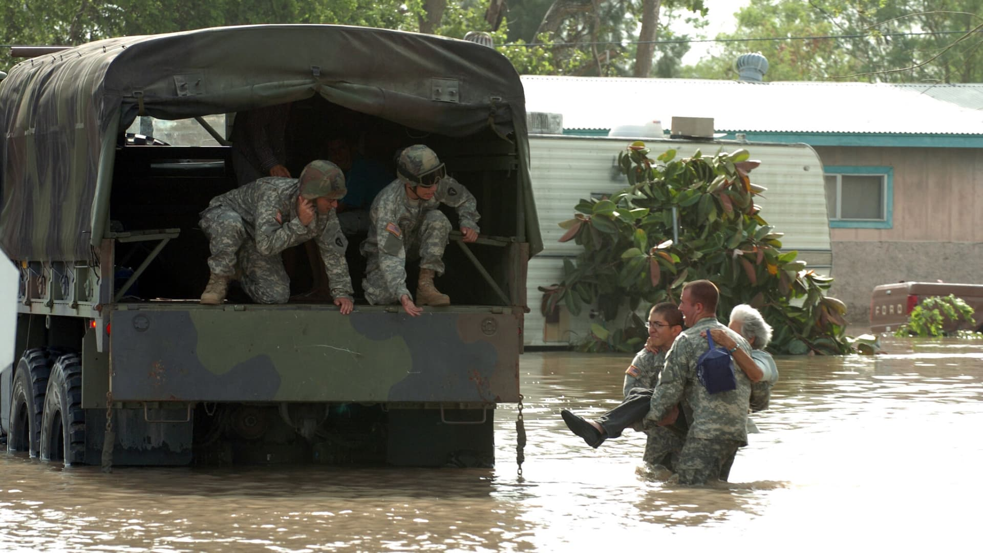 Texas National Guard Pvt. Mark Rivera of Co. A, 72nd Infantry Brigade, and Pvt. 1st Class Joseph Davora, Co. A, 1-41 Infantry Regiment, carry a woman stranded by flood waters to a waiting truck, where Pvt. John Paul Borrego and Pvt. 1st Class Christopher Culbelier, wait.