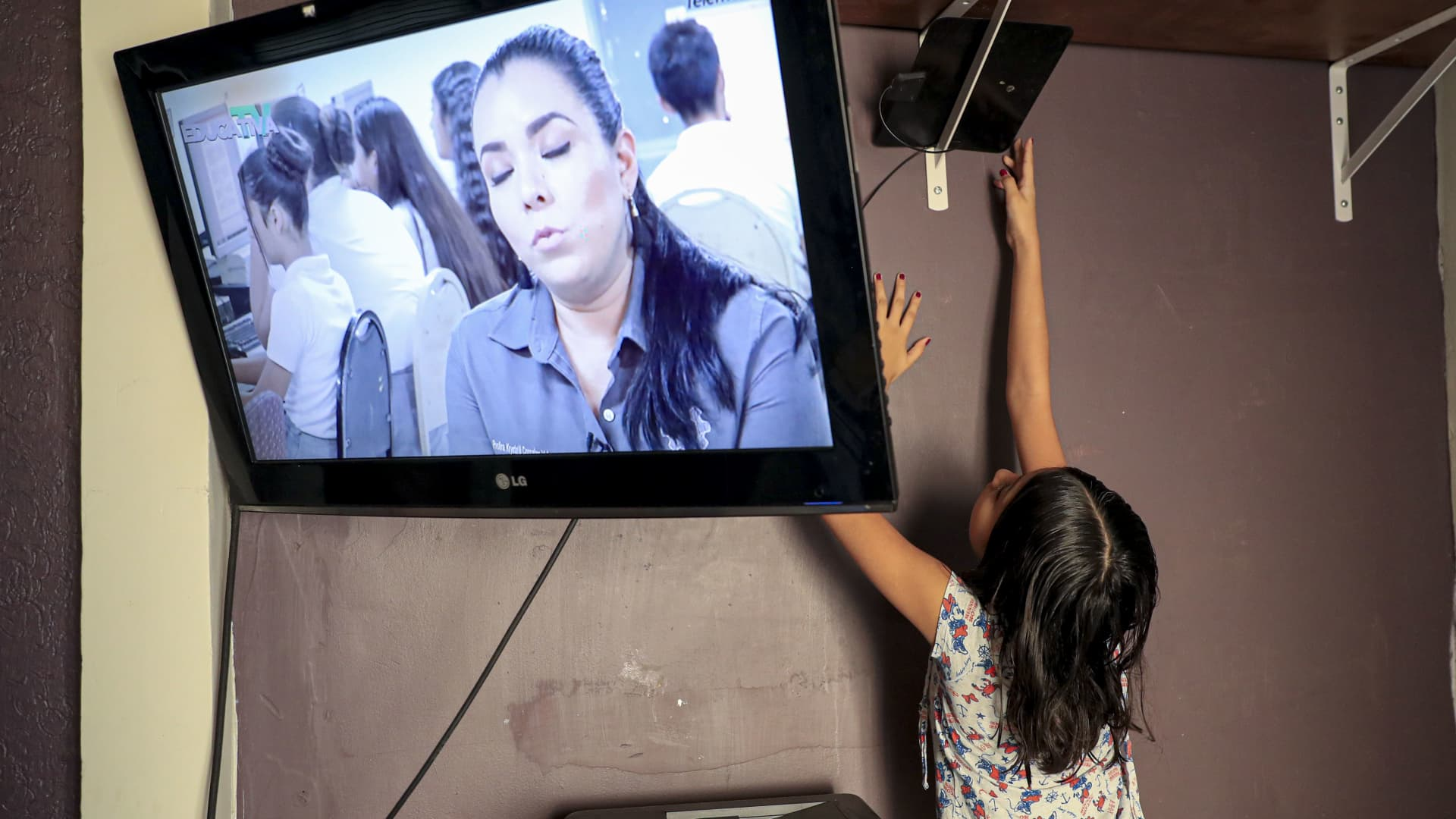 A young girl adjusts the antenna of a television in an attempt to obtain a digital signal.