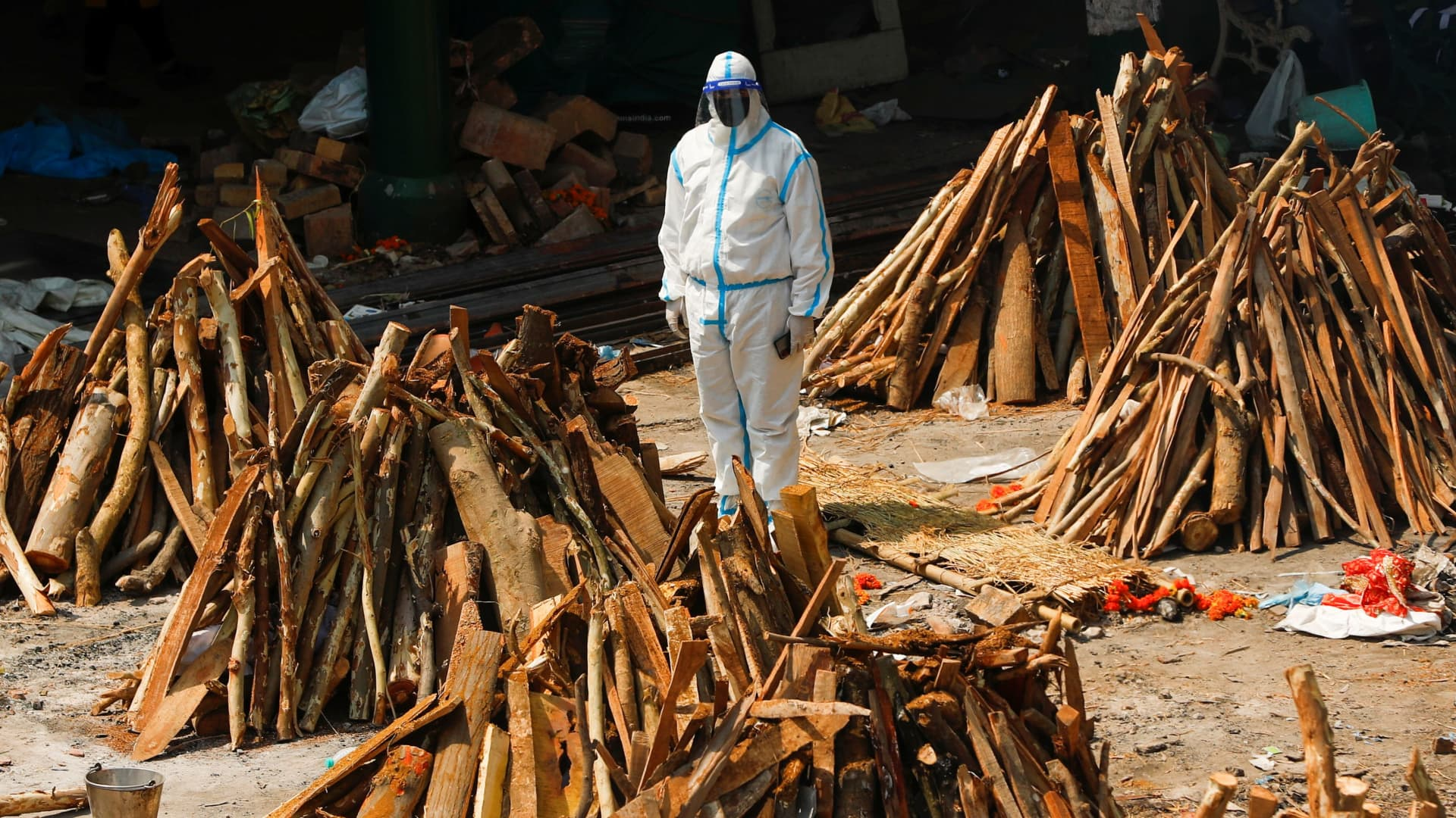 A man wearing personal protective equipment (PPE) stands next to funeral pyres of those who died from the coronavirus disease (COVID-19), during a mass cremation, at a crematorium in New Delhi, India April 26, 2021.