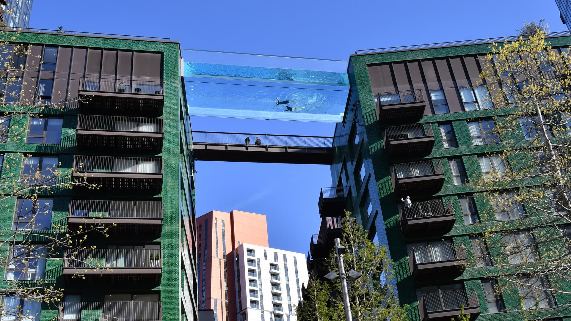 Models swim in a transparent acrylic swimming pool bridge that is fixed between two apartment blocks at Embassy Gardens next to the new U.S. Embassy in south-west London on April 22, 2021.