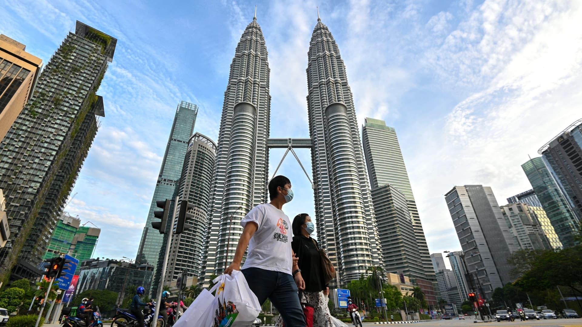 People wearing face masks walk in front of the Petronas Twin Towers in Kuala Lumpur, Malaysia, Jan. 29, 2021.