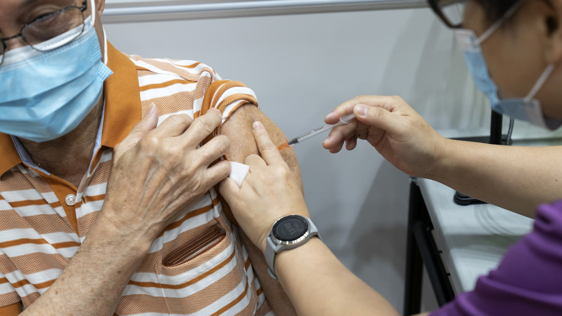 A health worker administers the Pfizer-BioNTech Covid-19 vaccine to a senior citizen at the Senja-Cashew Community Centre Vaccination Centre, operated by Thomson Medical, in Singapore, on Monday, March 8, 2021. Singapore is introducing a program calledConnect@Changithat will allow people to enter the island for business and official purposes without having to quarantine, provided they stay in abubble-like facilitynear Changi Airport for the duration of their visit. Photographer: Wei Leng Tay/Bloomberg via Getty Images