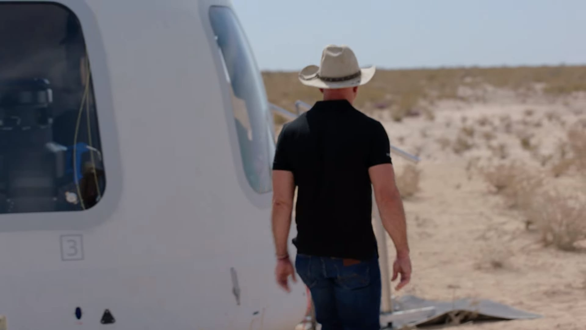 Jeff Bezos walks out to where the New Shepard capsule landed in the Texas desert after a test flight in April 2021.