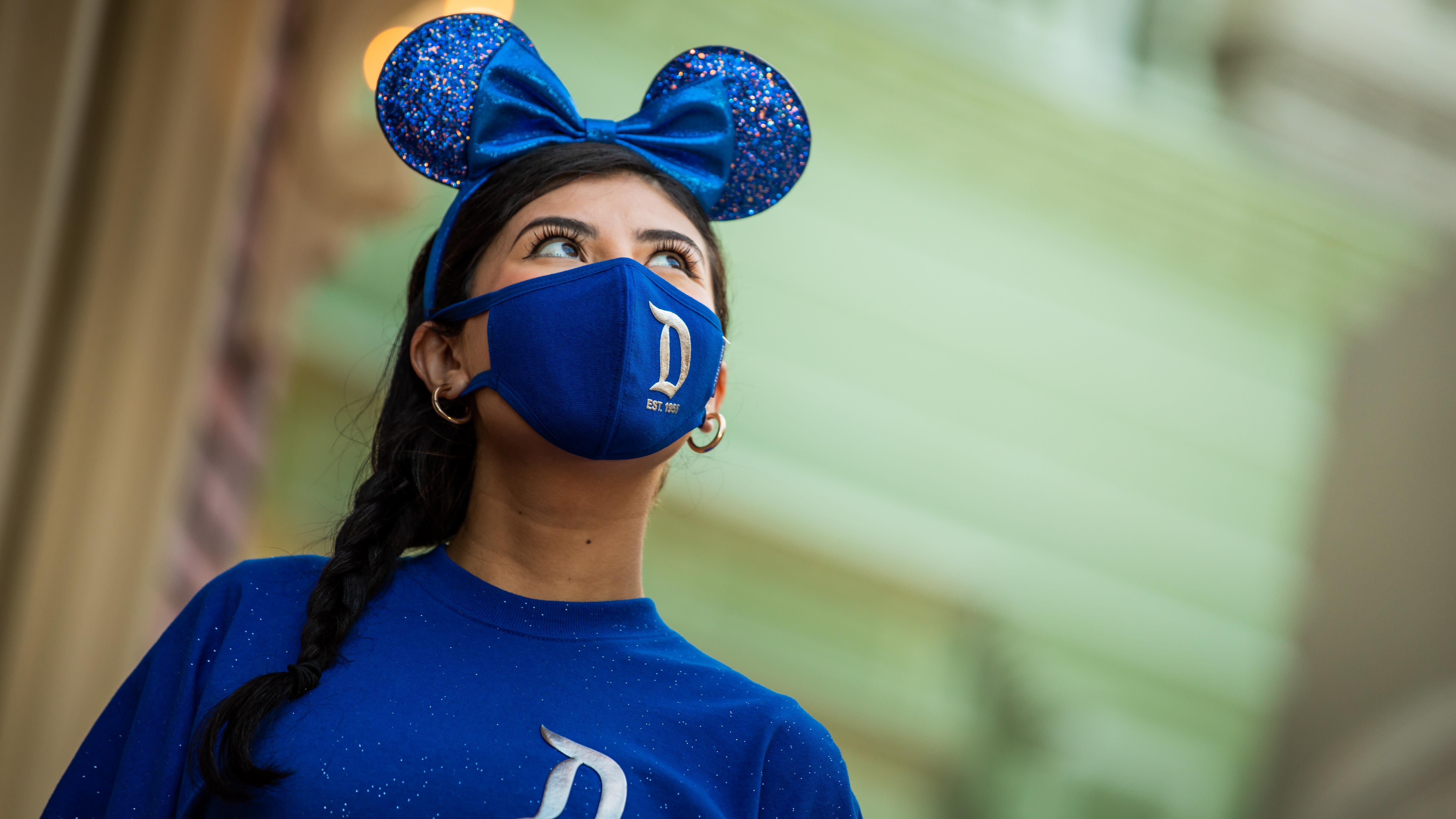 Pengikut Disney merayakan pembukaan kembali Disneyland dengan indera pendengaran dan topeng Mickey yang diadaptasi thumbnail