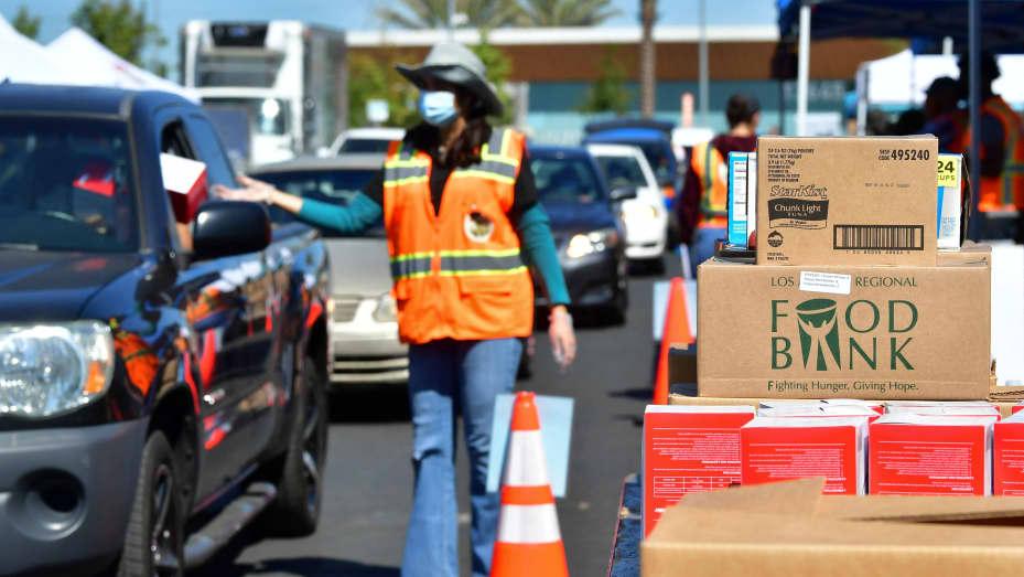 Các nhân viên của Ngân hàng Lương thực Khu vực Quận Los Angeles giúp phân phát thực phẩm cho khoảng 2.000 xe dự kiến sẽ đến Willowbrook, California vào ngày 29 tháng 4 năm 2021 trong một nỗ lực không ngừng để giúp đỡ những người bị ảnh hưởng bởi đại dịch coronavirus.