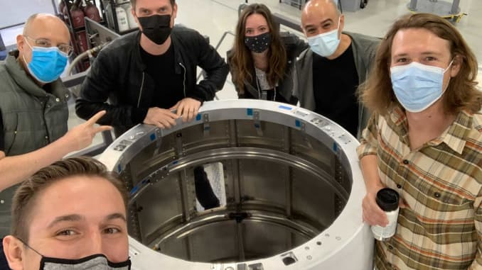Members of Astra's leadership team gatherered around a rocket interstage in production, from right: VP of manufacturing Bryson Gentile, SVP of factory engineering Dr. Pablo Gonzalez, VP of communications Kati Dahm, founder and CEO Chris Kemp, EVP of engineering Benjamin Lyon.