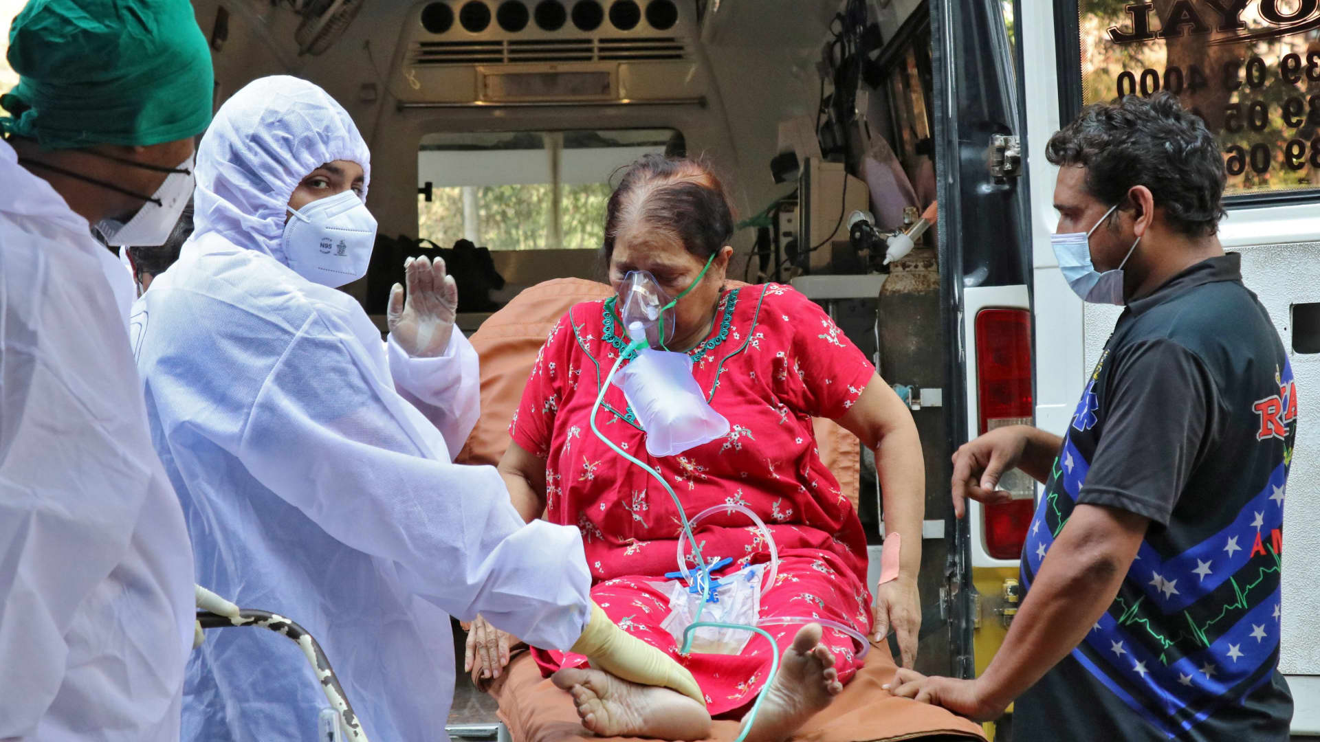 Healthcare workers and relatives carry a woman from an ambulance for treatment at a COVID-19 care facility, amidst the spread of the coronavirus disease (COVID-19) in Mumbai, India, May 4, 2021.