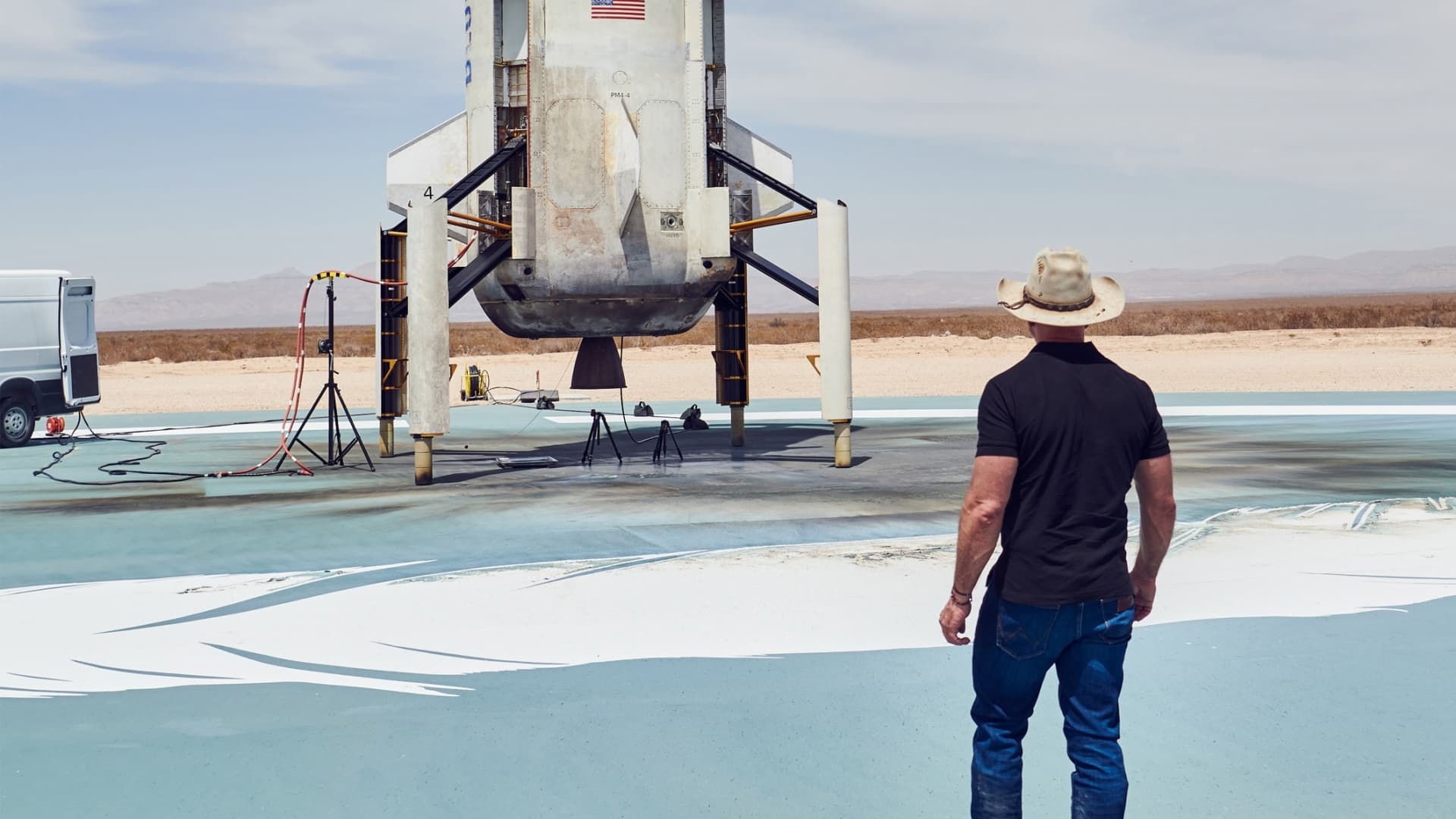 Jeff Bezos takes a look at the New Shepard rocket booster on the landing pad after a successful NS-15 flight and landing in April 2021.
