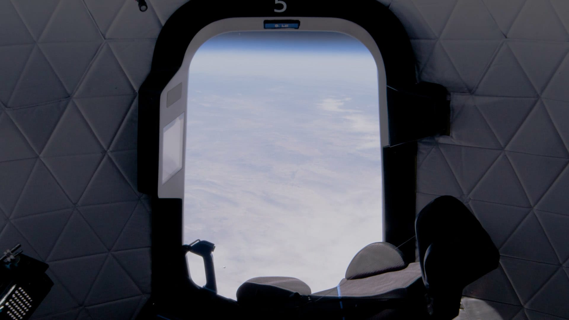 A seat and the view from inside a New Shepard capsule at the edge of space.