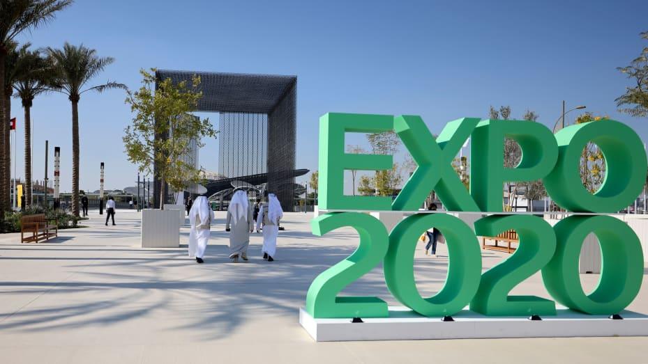 People walk past the official sign marking the Dubai Expo 2020 near the Sustainability Pavilion in Dubai, United Arab Emirates, on January 16, 2021.