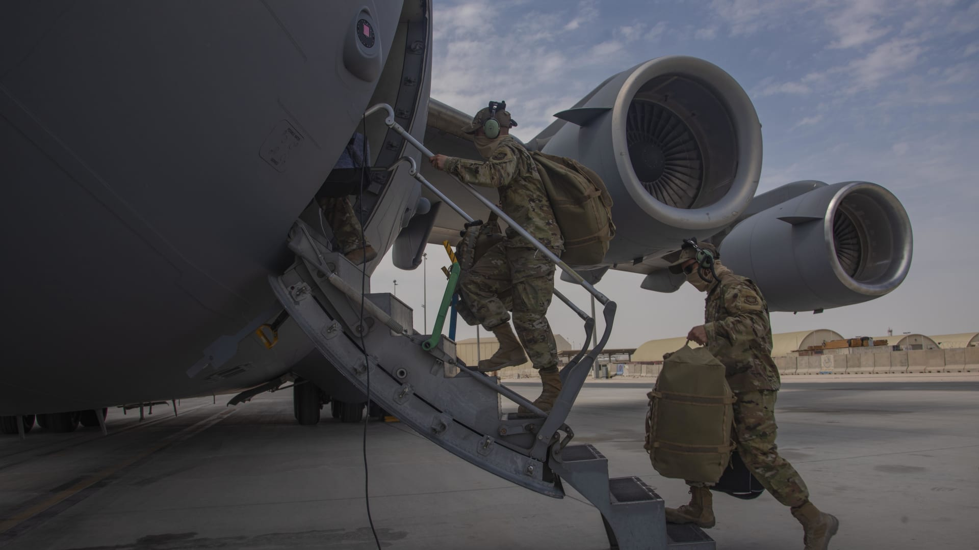 Aircrew assigned to Al Udeid Air Base, Qatar, carry their gear into a C-17 Globemaster III assigned to Joint Base Charleston, South Carolina, April 27, 2021.