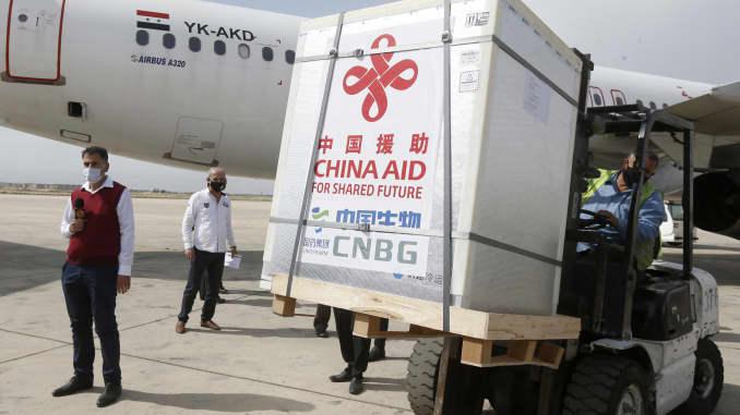 Pekerja membongkar kotak berisi vaksin Sinopharm Covid19, yang disumbangkan oleh China, di Bandara Internasional Damaskus pada 24 April 2021, di ibu kota Suriah