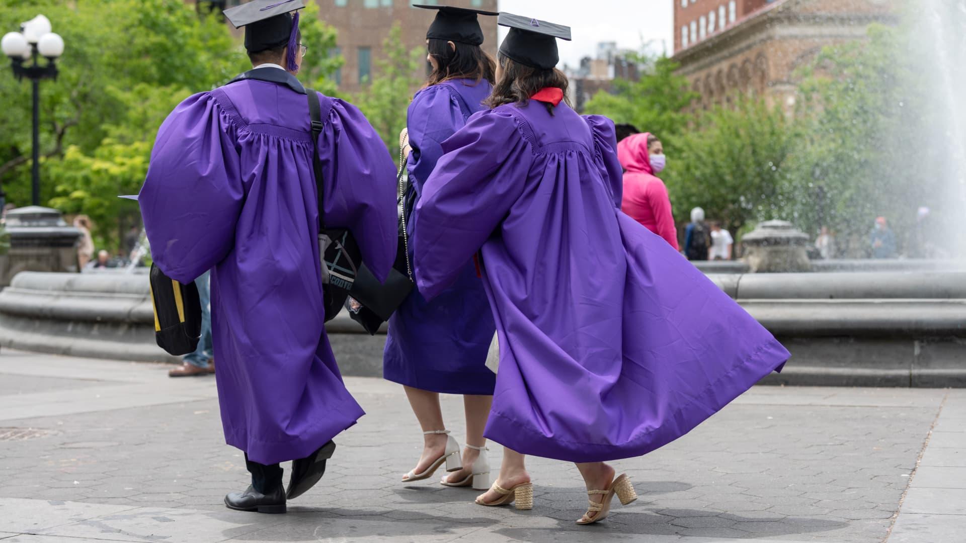 New York University graduates walk through New York's Washington Square Park on May 9, 2021.