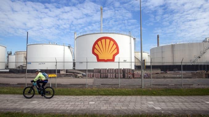 Seorang pengendara sepeda melewati silo minyak di kilang Royal Dutch Shell Pernis di Rotterdam, Belanda, pada Selasa, 27 April 2021