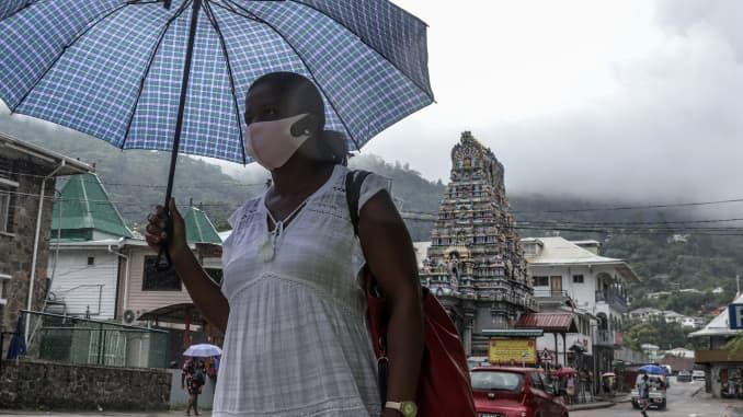 Seorang wanita yang memegang payung berjalan di jalan di ibu kota Seychelles, Victoria