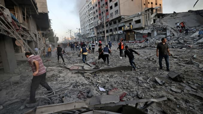 Rescuers and people gather amidst the rubble in front of Al-Sharouk tower that collapses after being hit by an Israeli air strike, in Gaza City, on May 12, 2021.