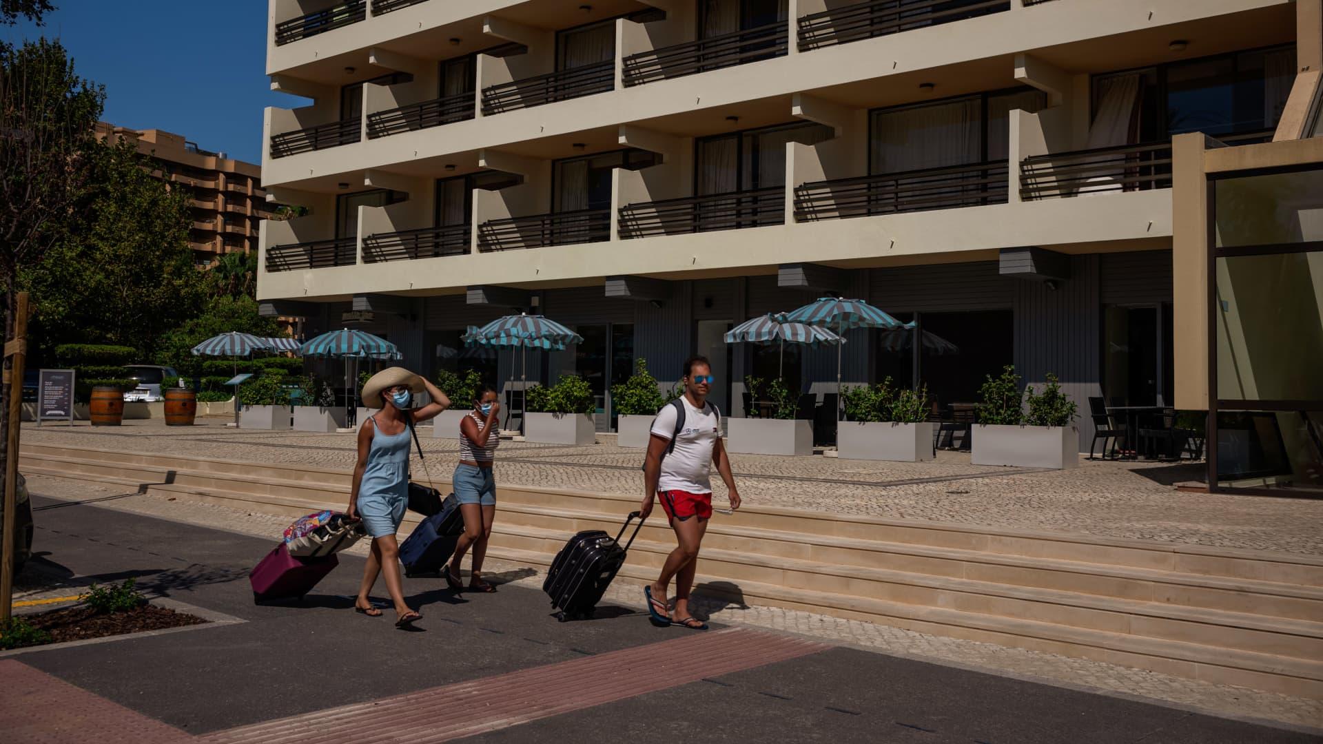 Tourists pull luggage as they walk towards a hotel at Villamoura beach in Villamoura, Algarve region, Portugal.