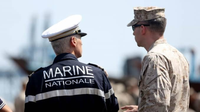 U.S. Marine Maj. Christopher Warnagiris interacts with a French Navy officer during the embarkation of the 15th Marine Expeditionary Unit aboard the French amphibious assault ship LHD Tonnerre (L9014)
