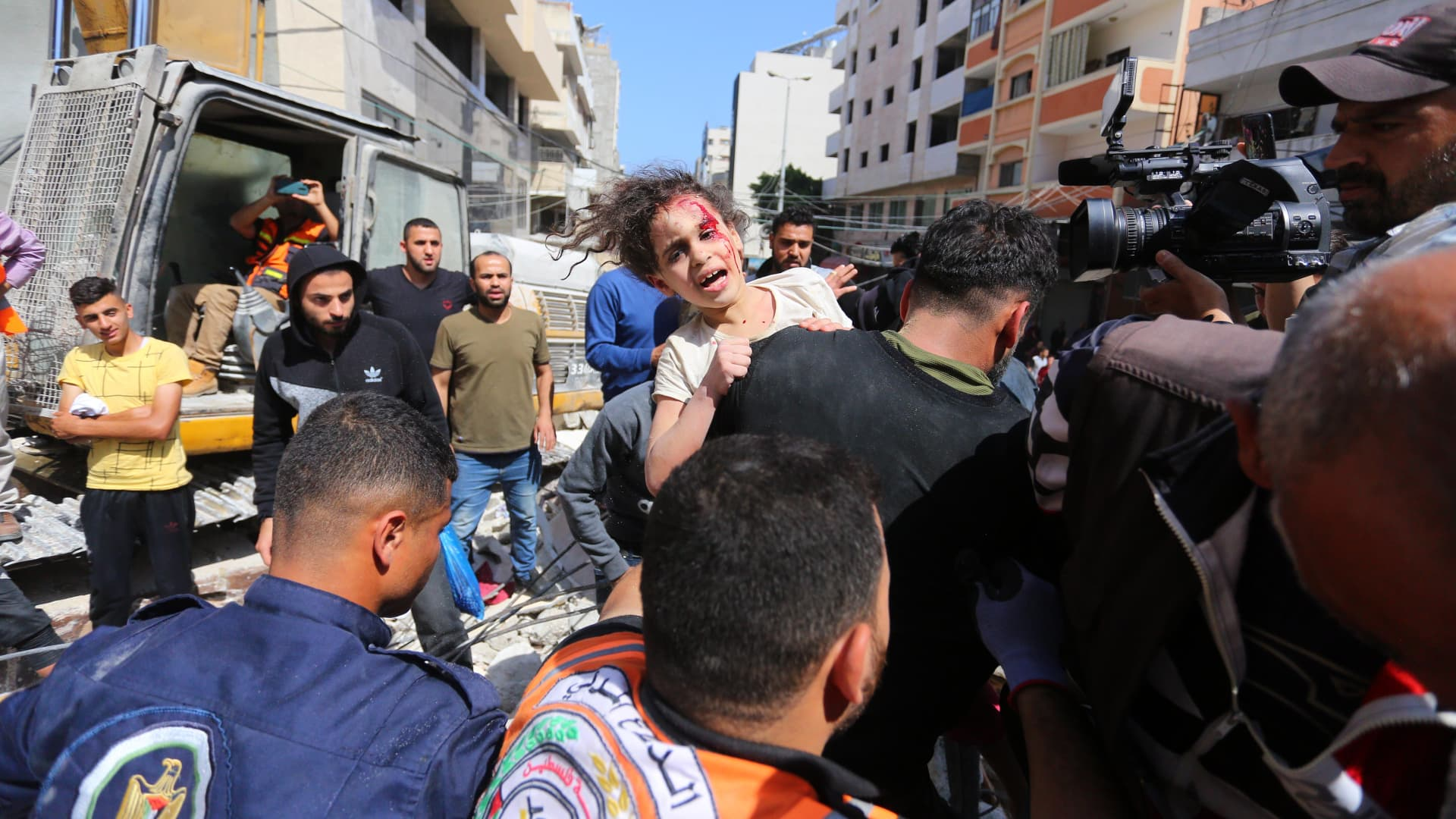 People rescue a wounded child from a debris as search and rescue works continue at a debris of a building after airstrikes by Israeli army hit buildings in al-Rimal neighborhood of Gaza City, Gaza on May 16, 2021.