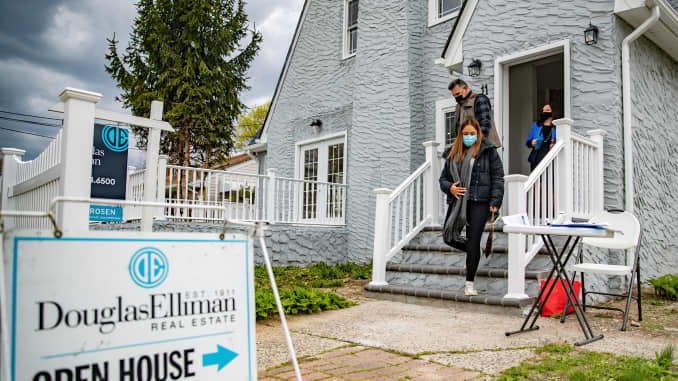 A real estate agent stands in the doorway as Giovani and Nicole Quiroz of Brooklyn, New York visit an open house in West Hempstead, New York on April 18, 2021.