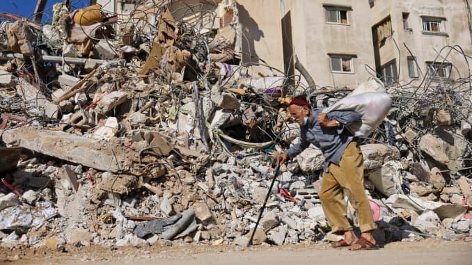 Seorang pria lansia Palestina berjalan melewati sebuah bangunan yang dihancurkan oleh pemboman Israel di Kota Gaza, pada 19 Mei 2021