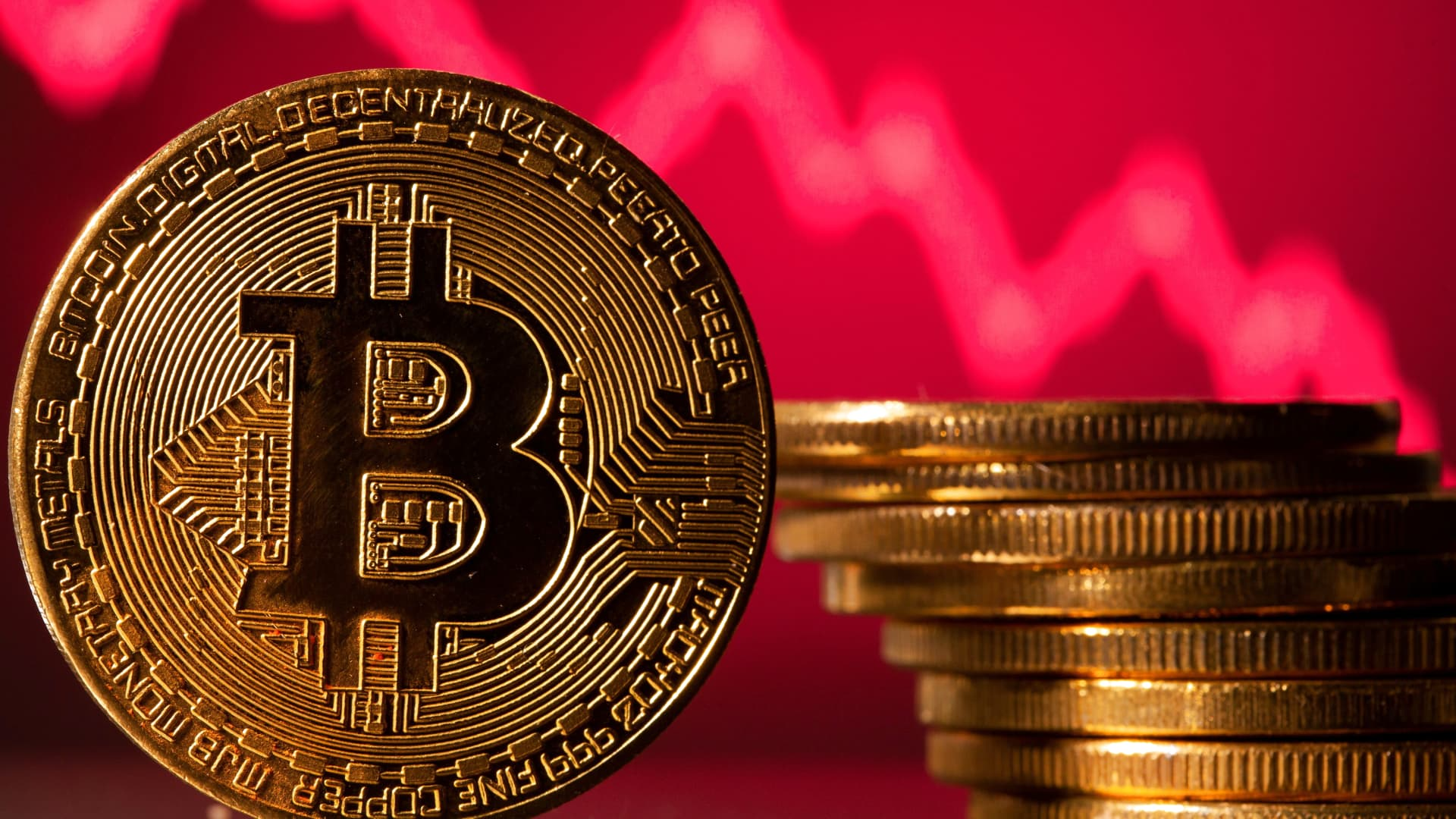 A representations of virtual currency Bitcoin is seen in front of a stock graph in this illustration taken May 19, 2021.