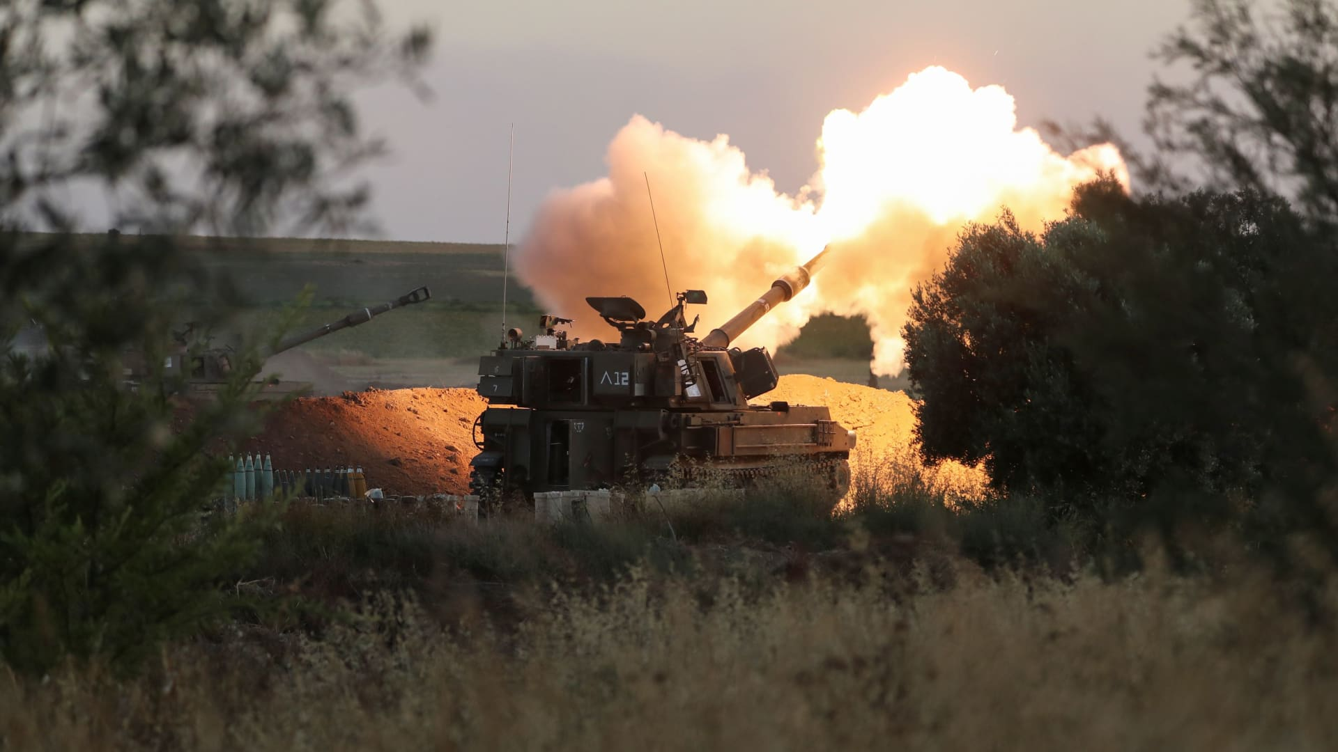 Israeli soldiers work in an artillery unit as it fires near the border between Israel and the Gaza strip, on the Israeli side May 19, 2021.