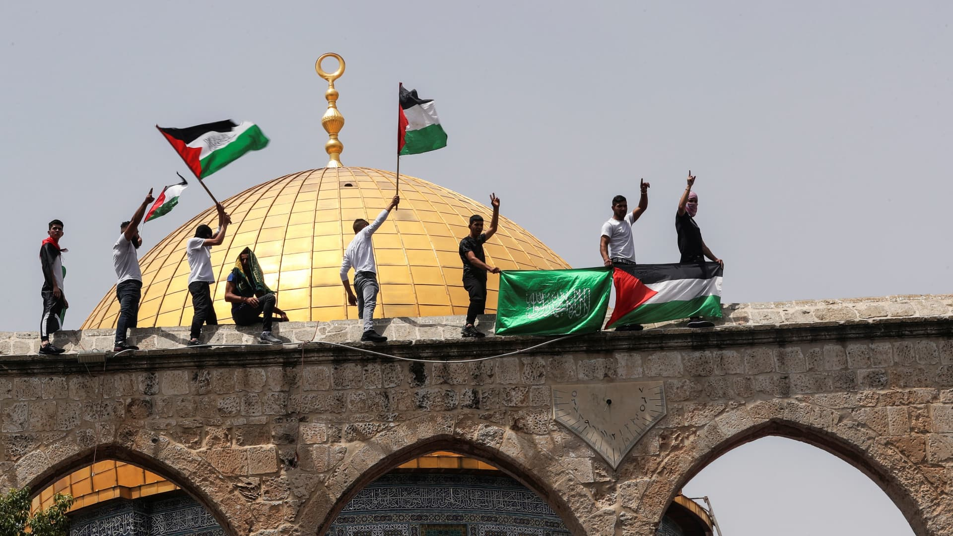 Palestinians hold flags as they stand at the compound that houses Al-Aqsa Mosque, known to Muslims as Noble Sanctuary and to Jews as Temple Mount, in Jerusalem's Old City May 21, 2021.