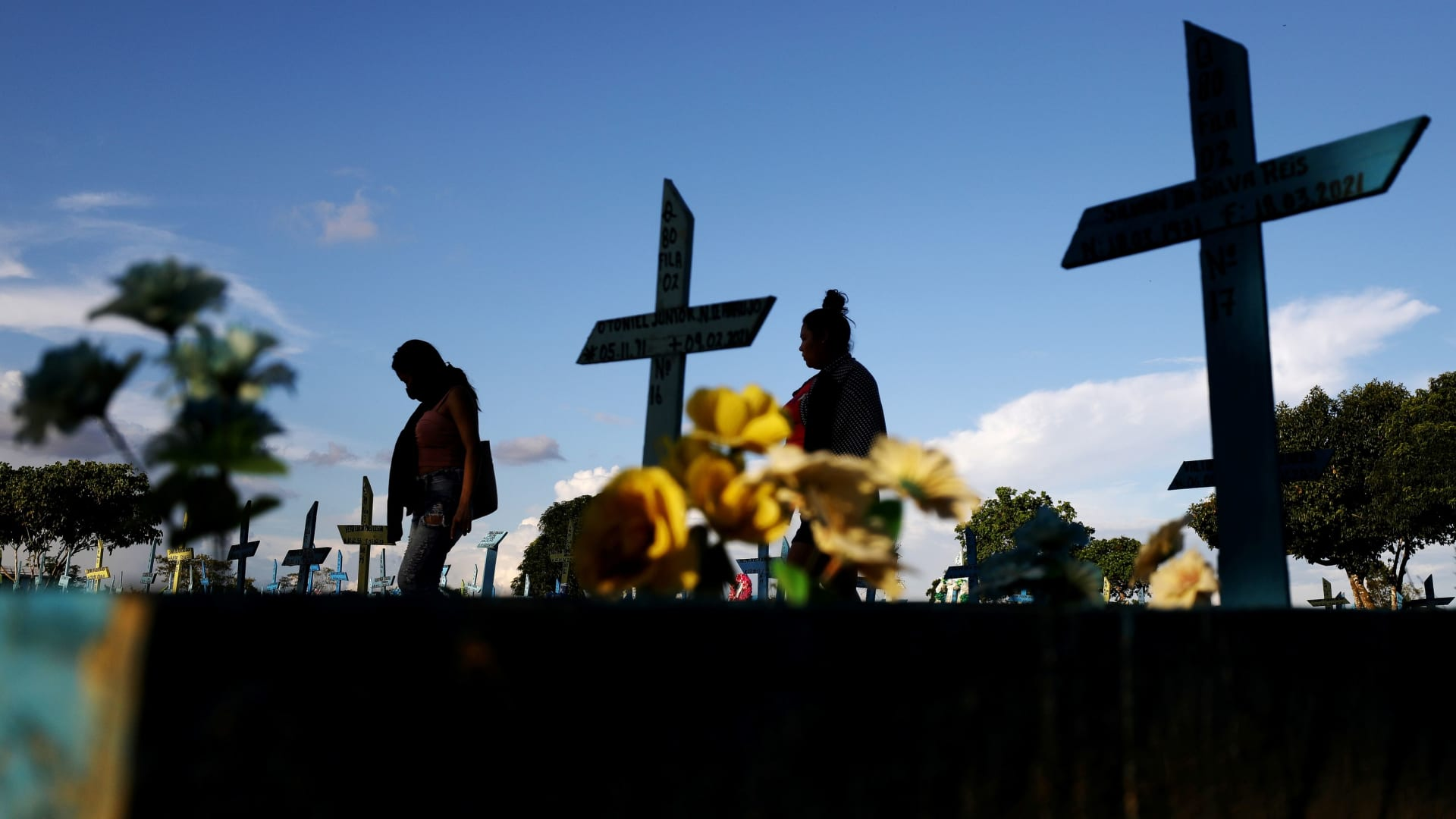 Two women walk next to graves of people who passed away due to the coronavirus disease (COVID-19) at the Parque Taruma cemetery in Manaus, Brazil May 20, 2021.