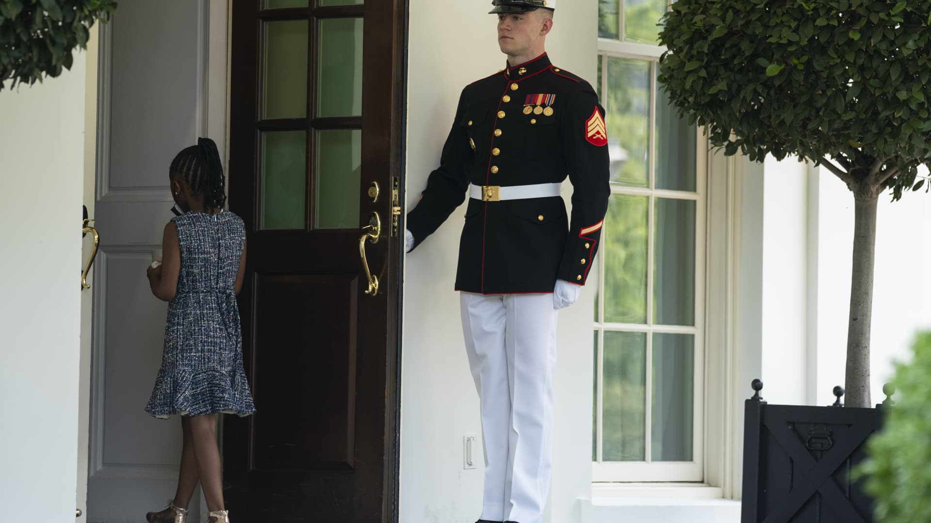 A Marine holds the door as Gianna Floyd, the daughter of George Floyd, walks into the White House, Tuesday, May 25, 2021, in Washington.