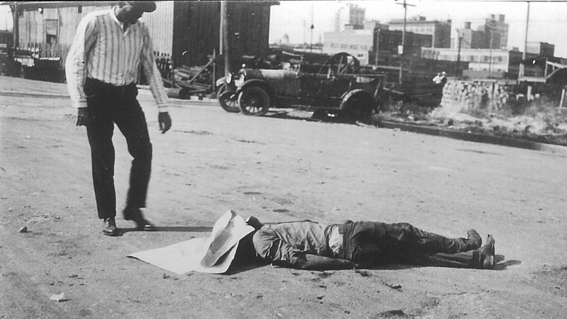 The body of an unidentified Black victim of the Tulsa race massacre lies in the street as a white man stands over him, Tulsa, Oklahoma, June 1, 1921.