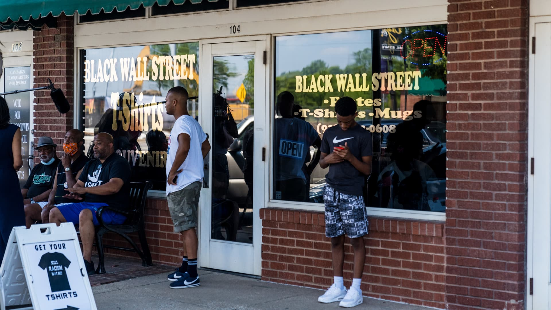 People stand outside the Black Wall Street T-Shirts and Souvenirs store at North Greenwood Avenue in the Greenwood District of Tulsa Oklahoma, U.S., on Thursday, June 18, 2020.