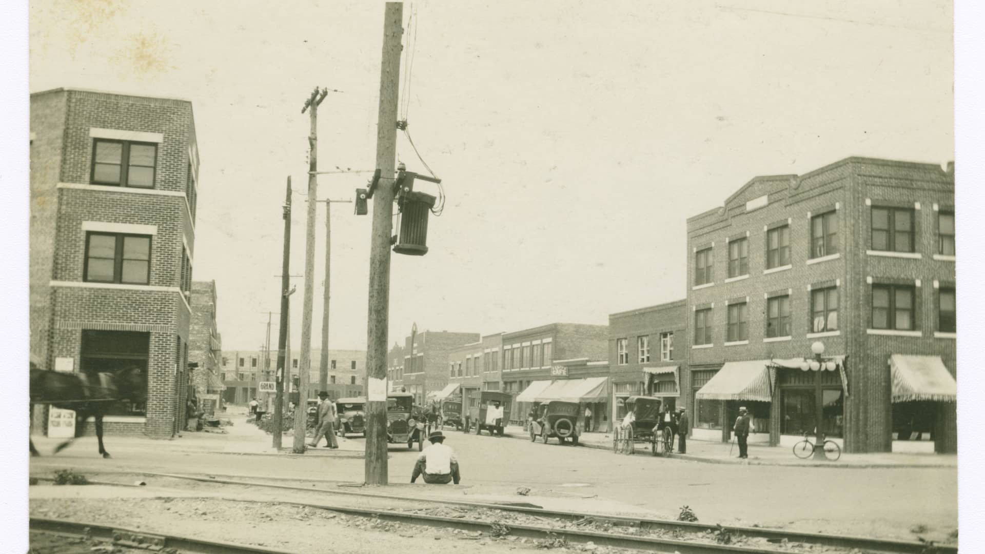 A black and white photograph of the Greenwood district in Tulsa, OK, with residents walking by shopfronts, before 1921.