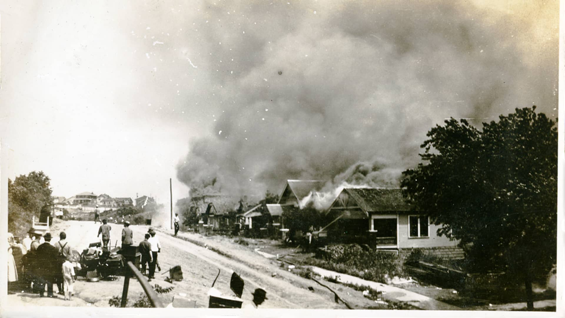 A group of people looking at smoke in the distance coming from damaged properties following the Tulsa, Oklahoma, racial massacre, June 1921.