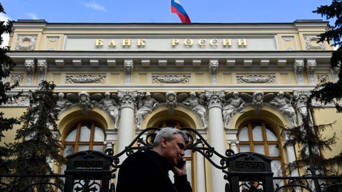 Một người đàn ông đang nghe điện thoại đi ngang qua trụ sở Ngân hàng Trung ương Nga khi lá cờ Nga tung bay, ở trung tâm thành phố Moscow, vào ngày 19 tháng 3 năm 2021.