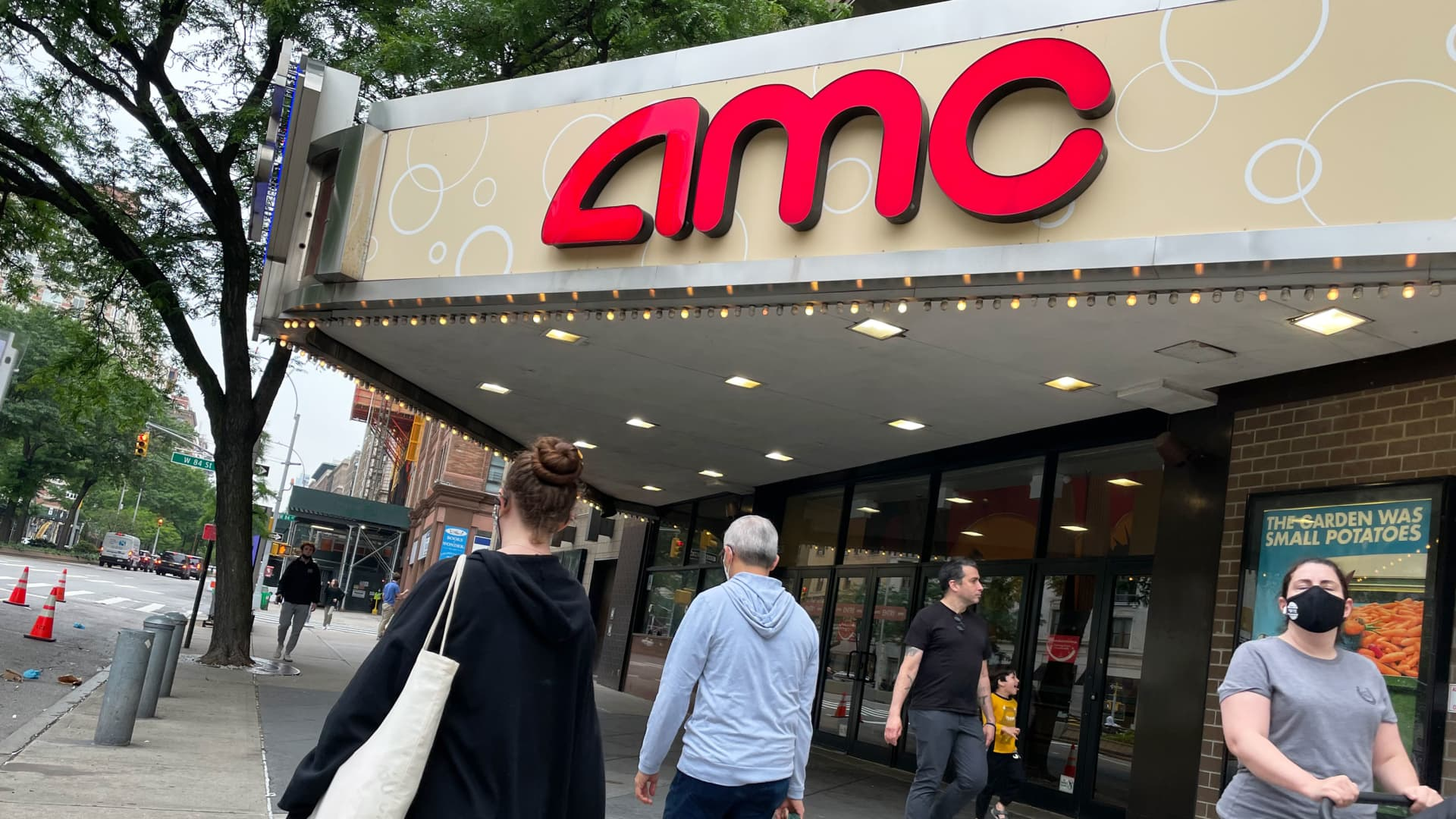 Pedestrians pass in front of an AMC theater in New York.