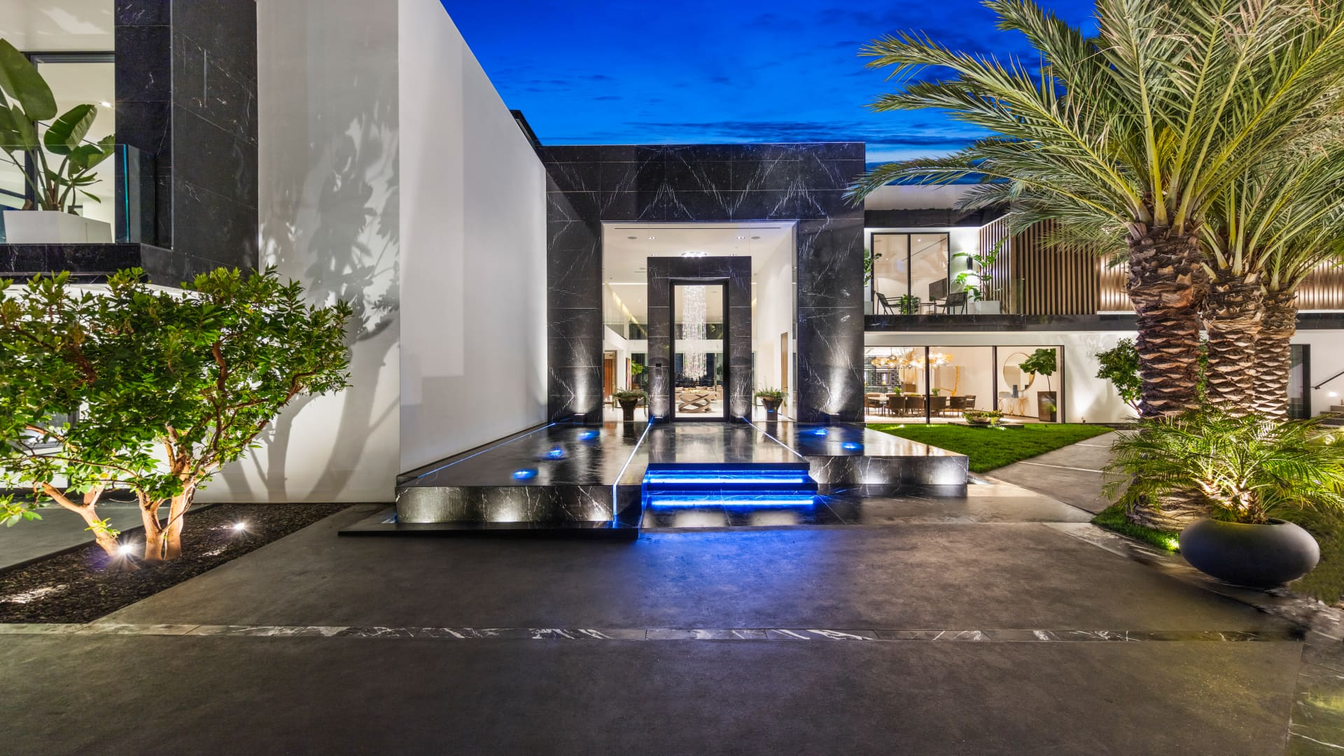 A black marble walkway leads to the home's 14-foot glass front door.