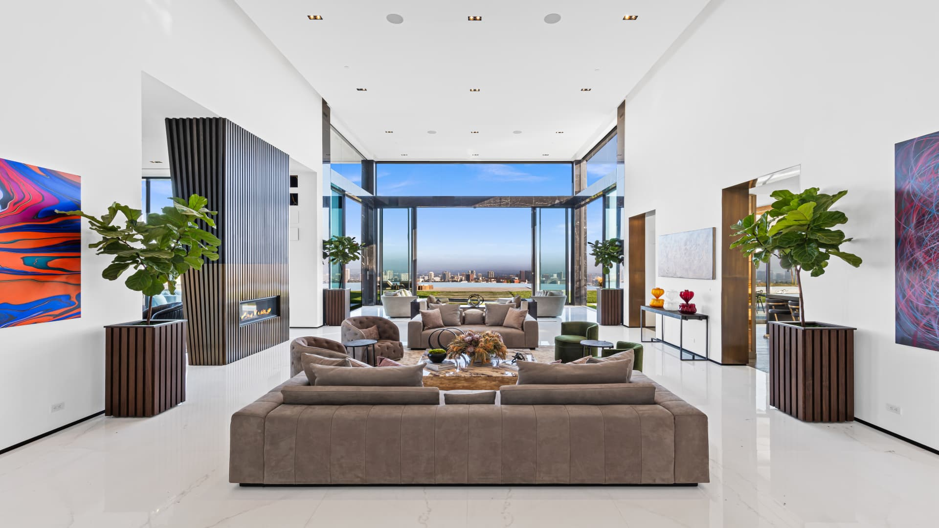The living room has 21-foot ceilings and a floor-to-ceiling glass wall that opens to the backyard.