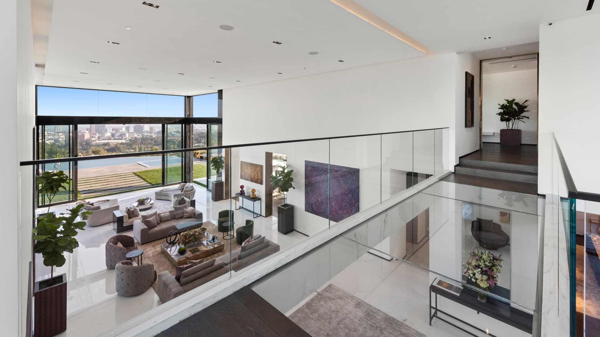 A glass-and-marble bridge overlooks the living room and leads to the owner's wing.
