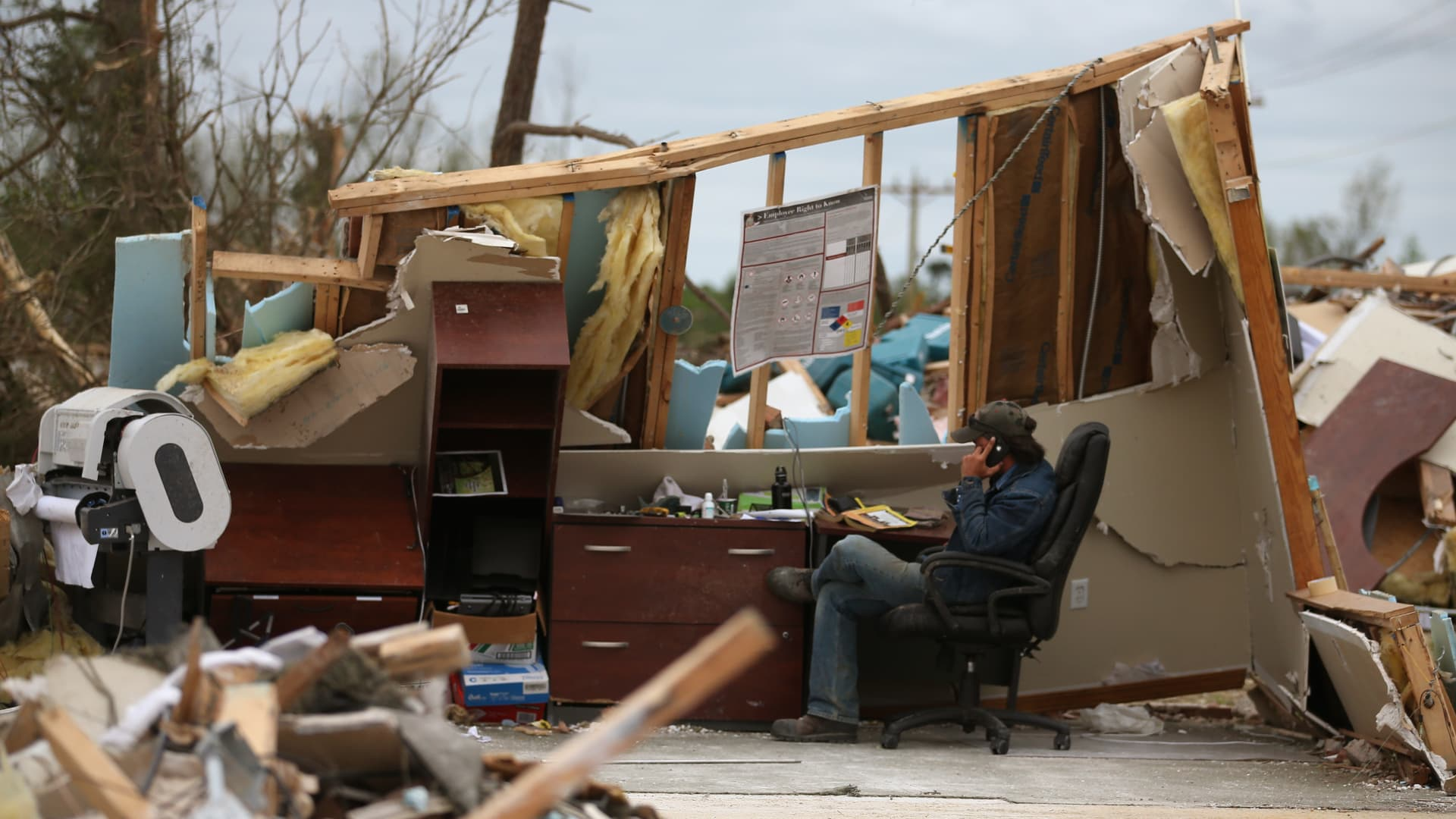 A man who wished not to be indentified talks on a phone in a business that was destroyed by a tornado in Mayflower, Arkansas.