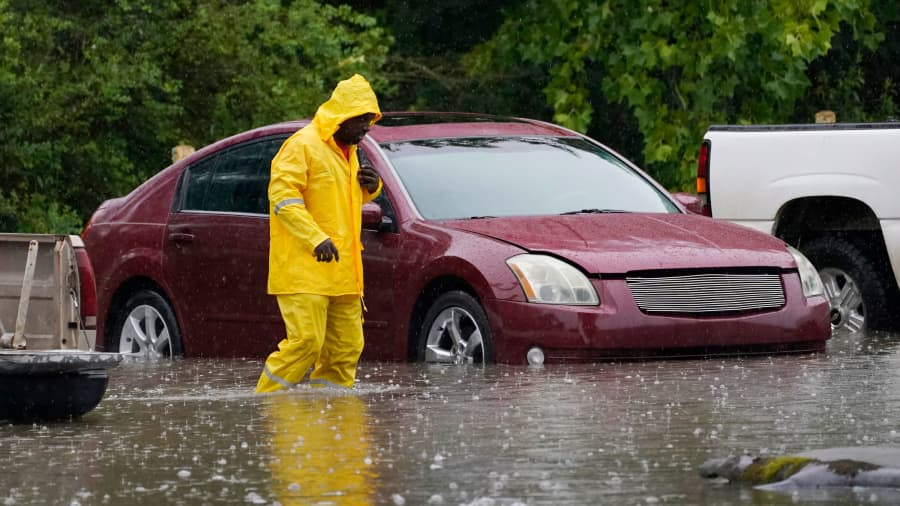 An employee at a used auto dealership treads water as he checks on vehicles they are moving out of the rising waters from two days of heavy rain in Lexington, Miss., Thursday, June 10, 2021.