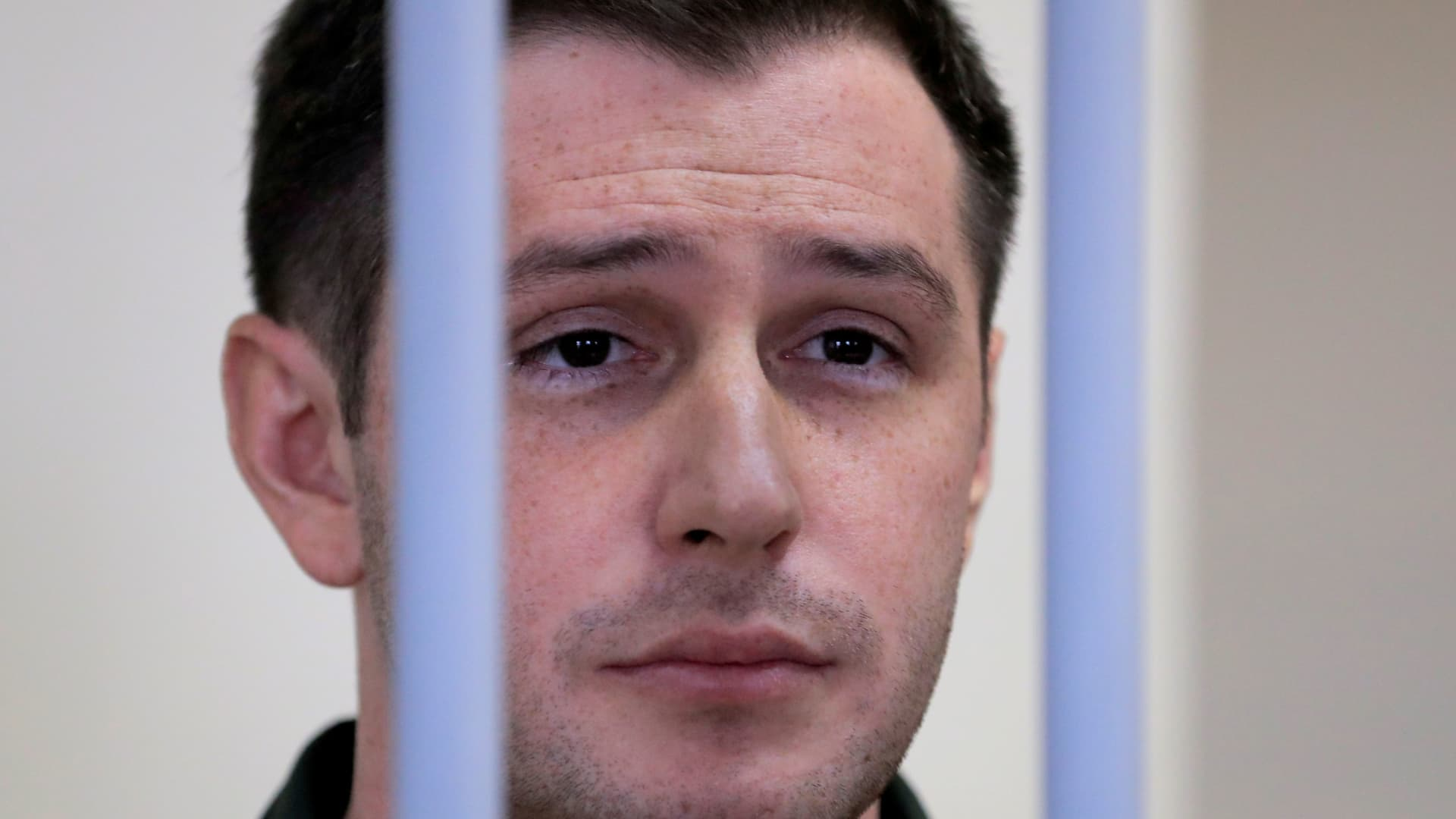 Former U.S. Marine Trevor Reed, who was detained in 2019 and accused of assaulting police officers, stands inside a defendants' cage during a court hearing in Moscow, Russia March 11, 2020.