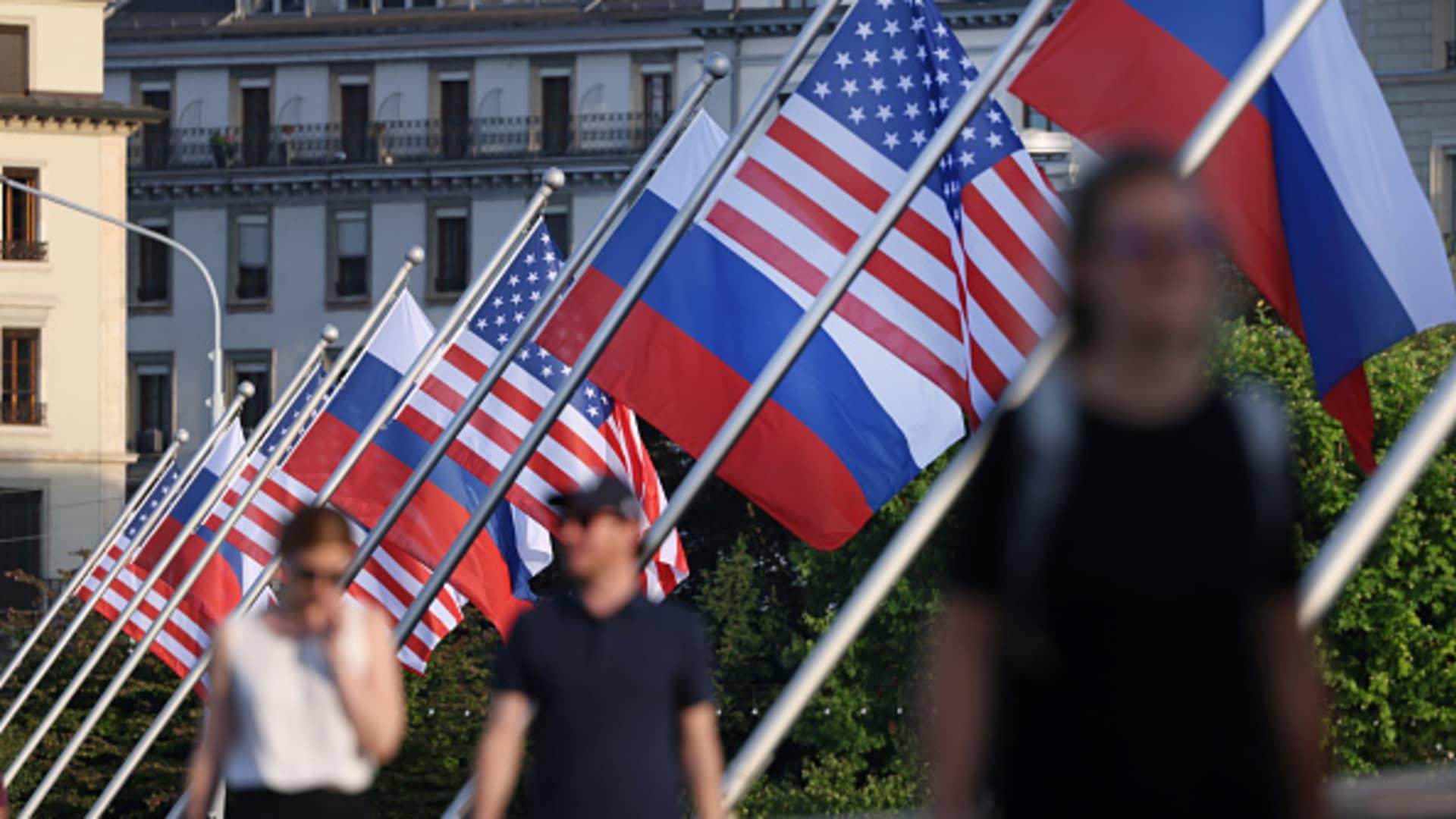 People walk under Russian and American flags on a bridge in the city center prior to a meeting between U.S. President, Joe Biden and Russian President, Vladimir Putin on June 15, 2021 in Geneva, Switzerland.