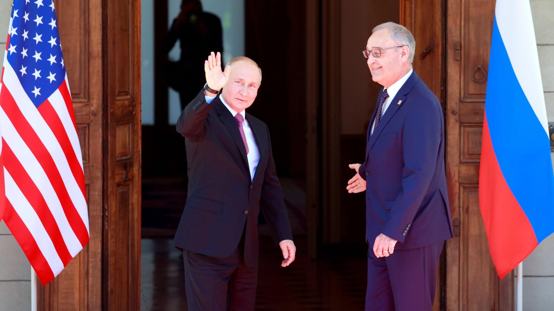 Russia's President Vladimir Putin waves next to Swiss President Guy Parmelin as he arrives at Villa La Grange for the U.S.-Russia summit, in Geneva, Switzerland, June 16, 2021.