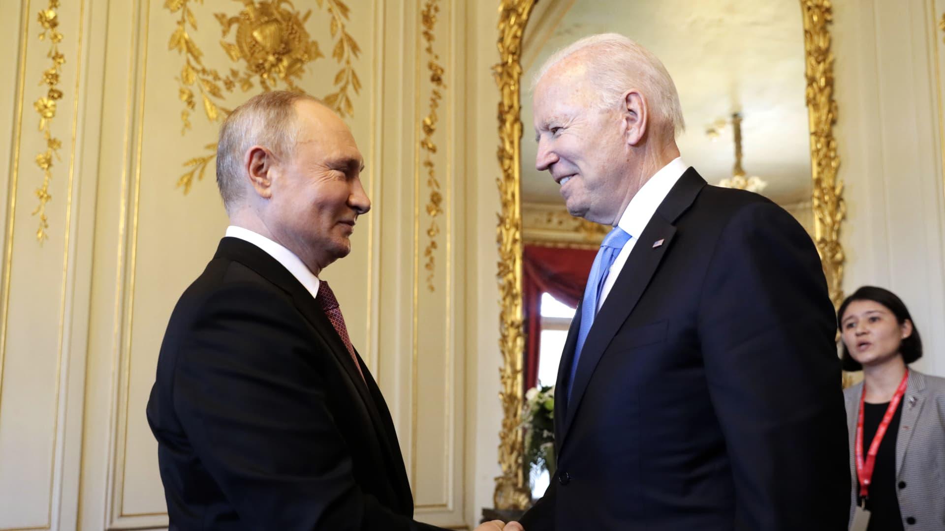 Russia's President Vladimir Putin (L) and US President Joe Biden shake hands as they meet for talks at the Villa La Grange.