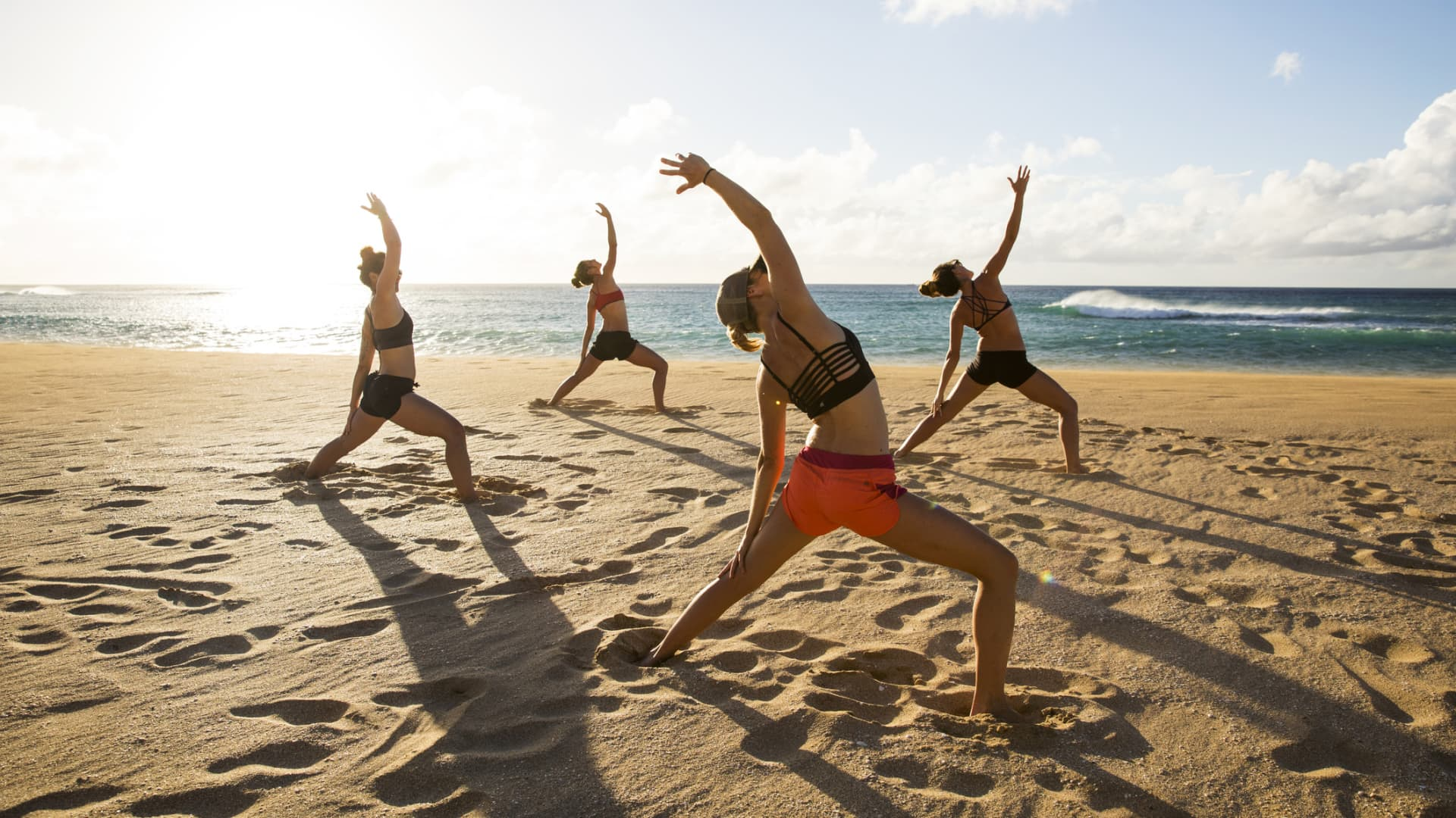 A group of friends enjoying some evening beach yoga while vacationing in Hawaii.