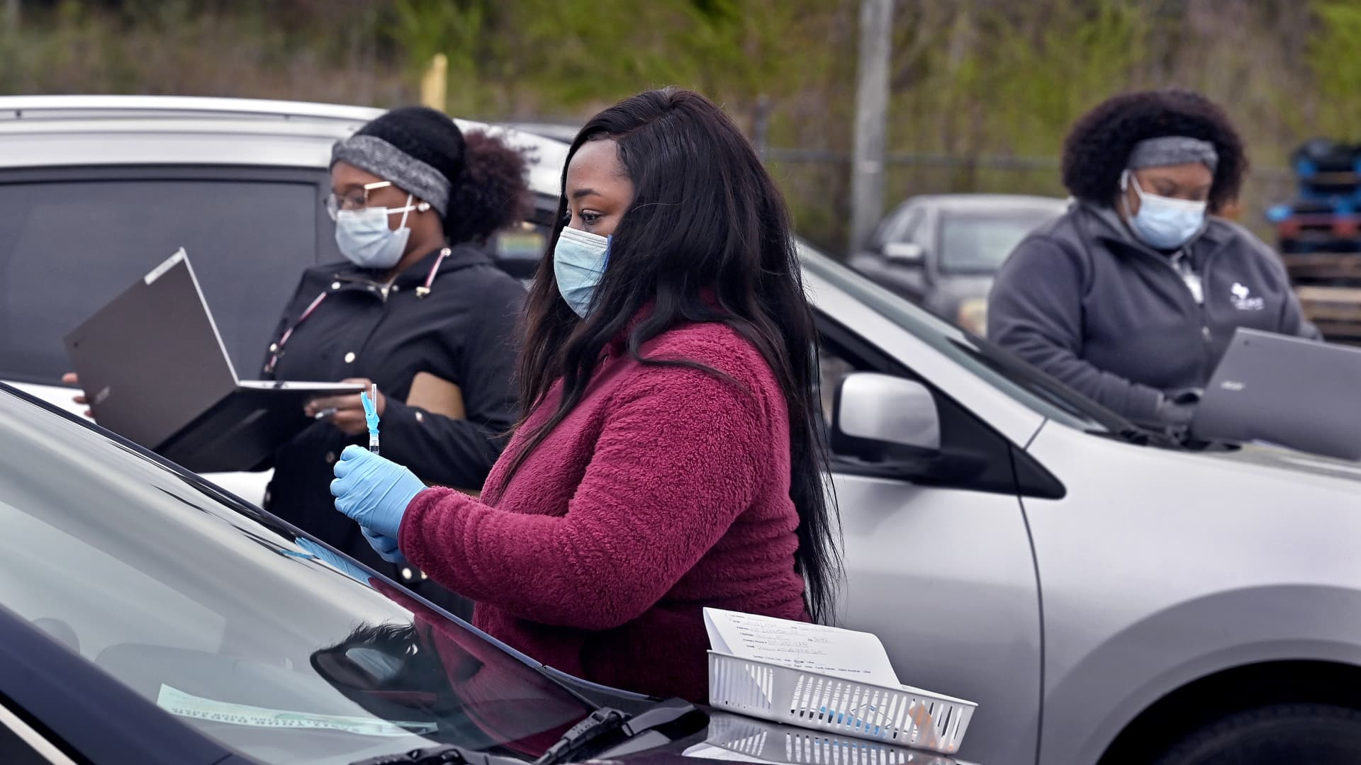 Lashondra Walter, (center), a nurse practitioner for Cahaba Medical Care gets ready to give a shot to a person in their car. She was joined by colleagues who roamed the parking lot with laptops to register people at the Linden National Guard Armory in Linden, Alabama on Friday, March 19, 2021.